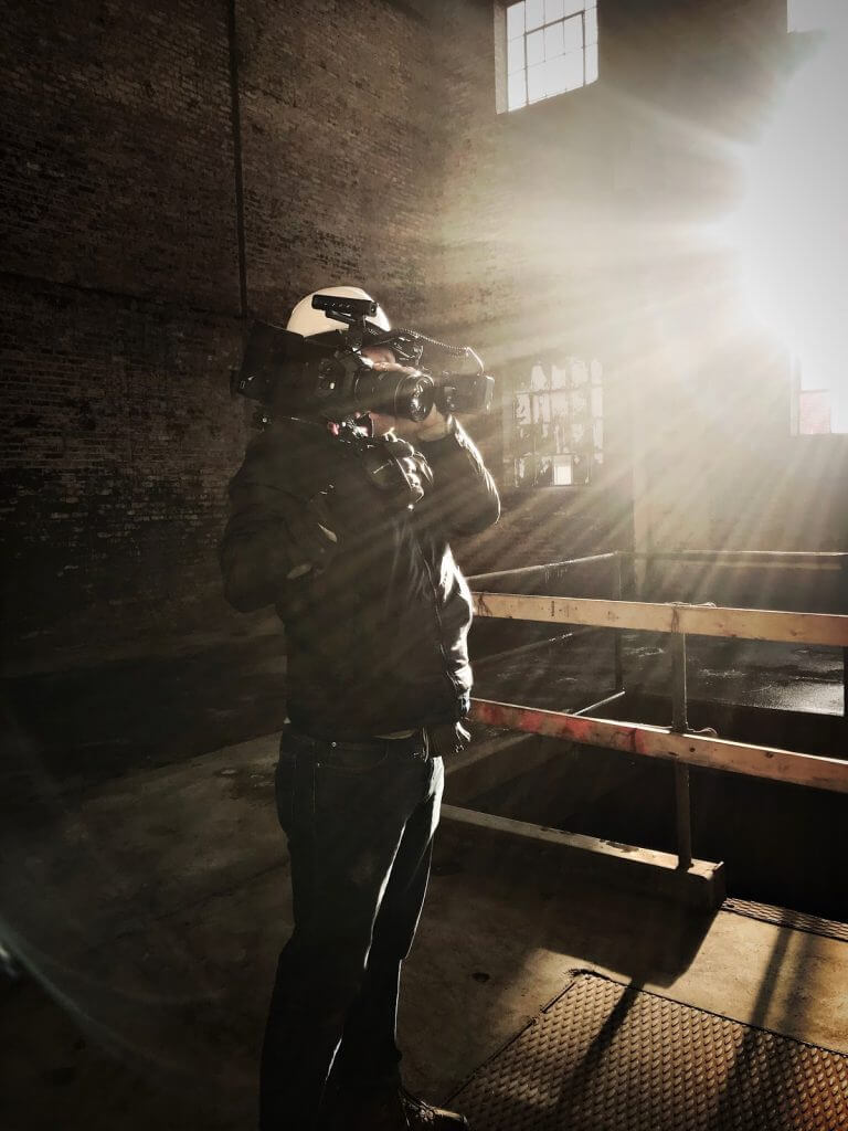 John films in an abandoned warehouse as a light shines into the camera